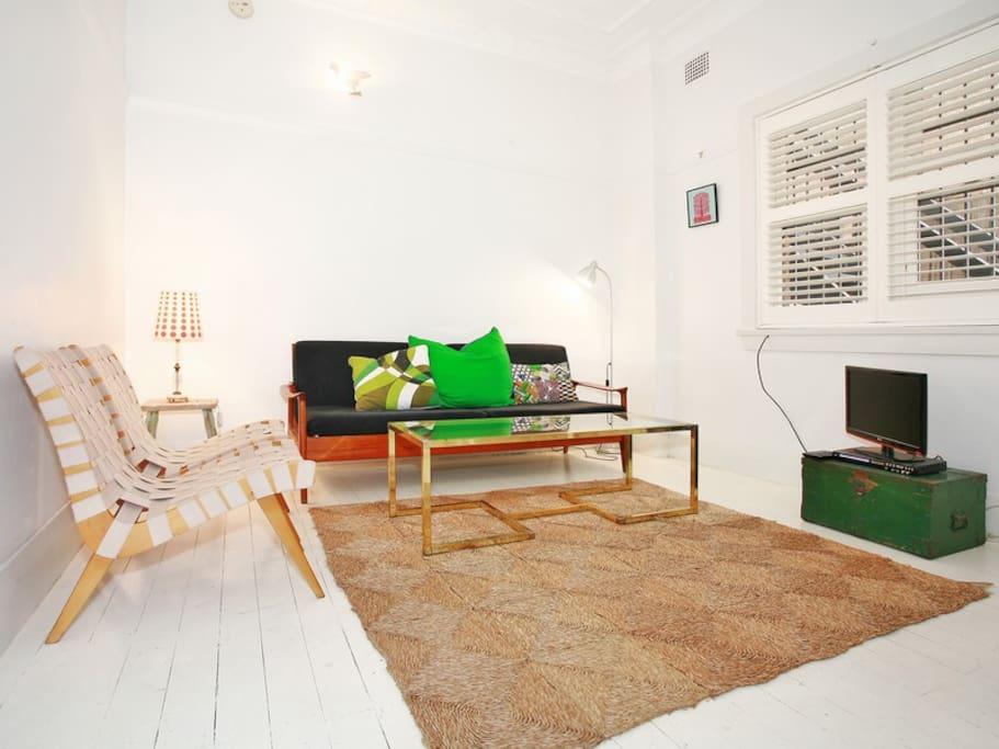 White-washed floor boards, seagrass matting and a mid-century sofa that converts to a double bed.