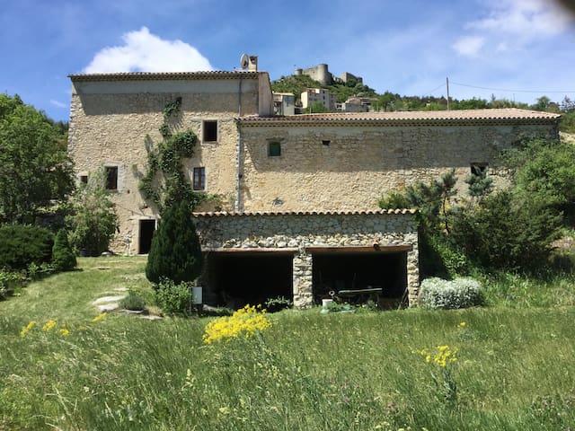Maison provençale en pierres entourée de verdure