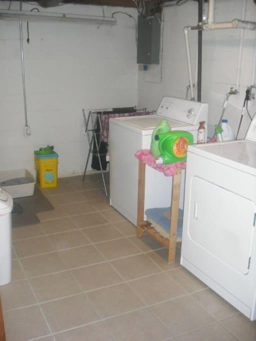 Laundry room in basement, with full sized fridge.