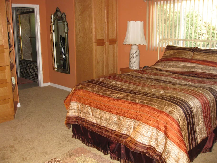 Master bedroom suite with queen bed and full bathroom in the back