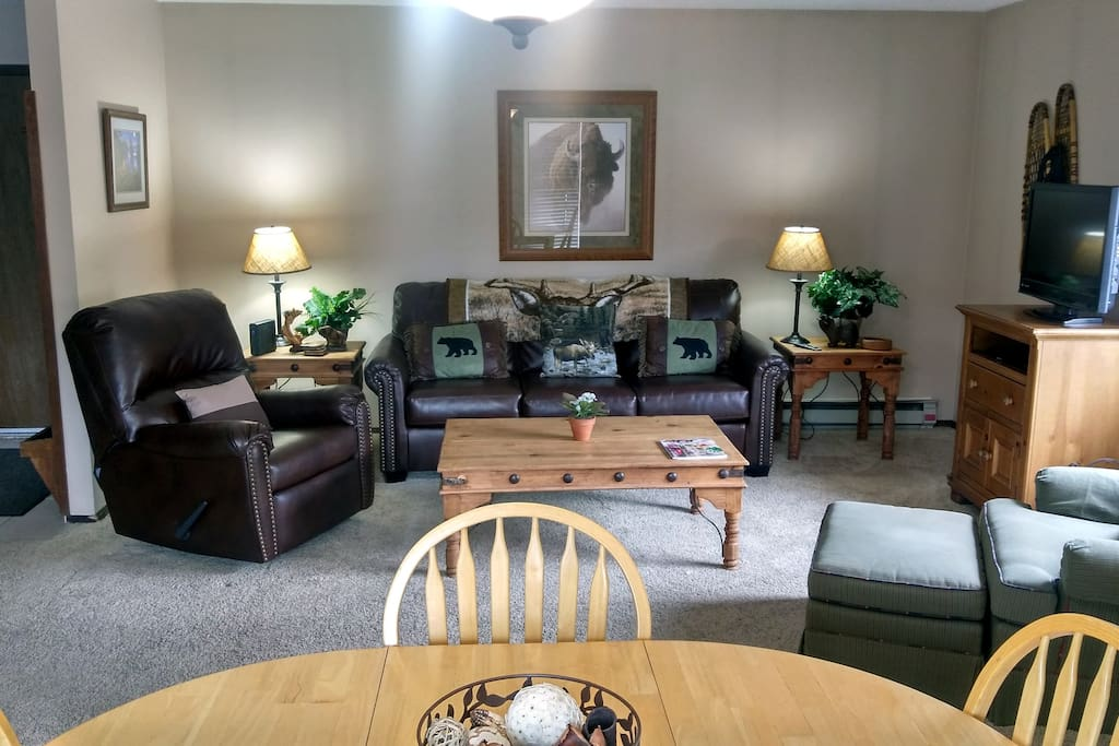 Beaver Creek West Condo F-2 living room with sofa bed, wood fireplace, dining table, and balcony w/ gas BBQ