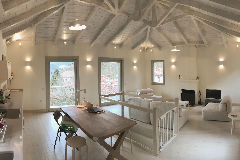 Ο ενιαίος χώρος (σαλόνι, τραπεζαρία, κουζίνα) με υπέροχη θέα προς τα γύρω βουνά και τον παραδοσιακό οικισμό του Μεγάλου Χωριού.