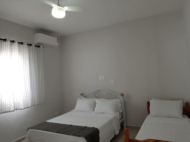 Segundo quarto, possui uma cama de casal, uma de solteiro, TV, ventilador de teto, colchões extras e uma cômoda para acomodar as roupas.