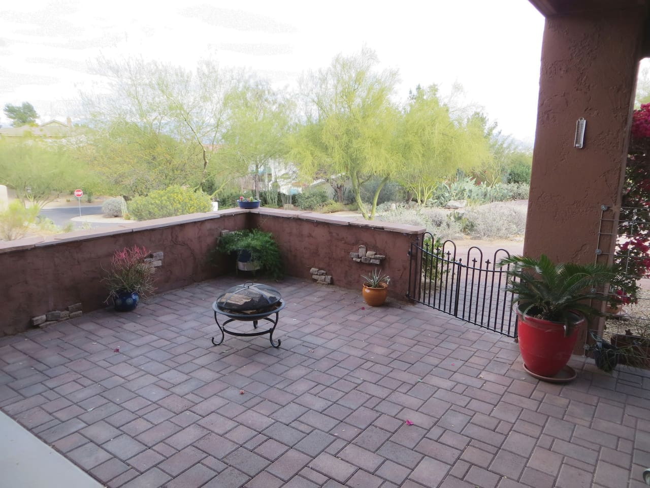 Intimate  paver Patio with lush desert fauna & mountain views.  On quiet residential street for taking in breathtaking  sunrises to the East.  Private off-street circle driveway parking beyond gate.