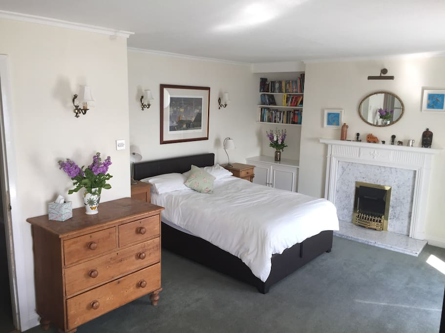 A large and light-filled bedroom with two large windows overlooking the harbour, a sofa and tea and coffee facilities.