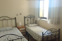 bedroom 2 with two single beds and air condition
