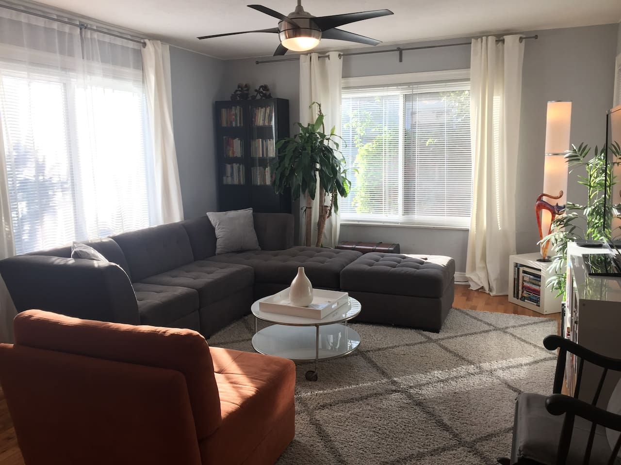 """Living room with a comfortable sofa , ceiling fan , 65"""" flat screen TV, Roku IV player"""