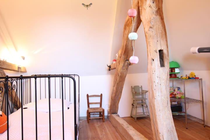 Le premier escalier du salon conduit à une petite chambre d'enfant avec deux lits une personne.
