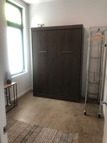Full size Murphy Bed in closed position with lots of natural light and optional rolling wardrobe-