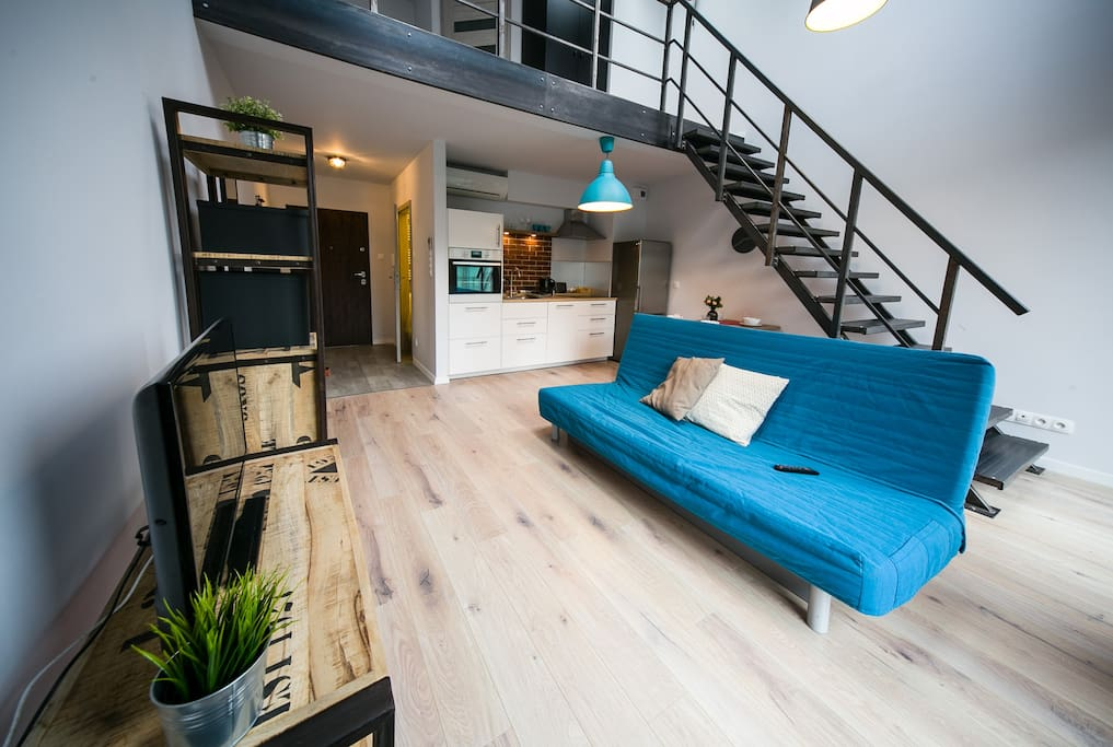 Bright living room with double sofa bed, flat screen TV, big windows and a dining area