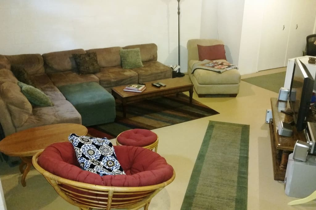"""Living room setup in basement with comfy sectional, chaise lounge and papasan chair.  42"""" TV connected to Dish Network and gaming consoles.  Includes mini-fridge and desk suitable for workspace (around corner)"""