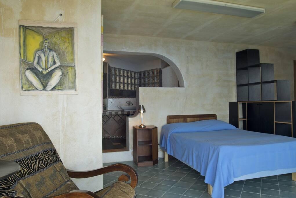 le coin chambre et salle d'eau, derrière les étagères; deux petits lits superposés
