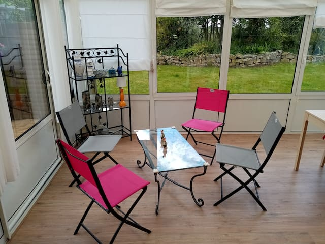 accès véranda avec salon et coin repas privé