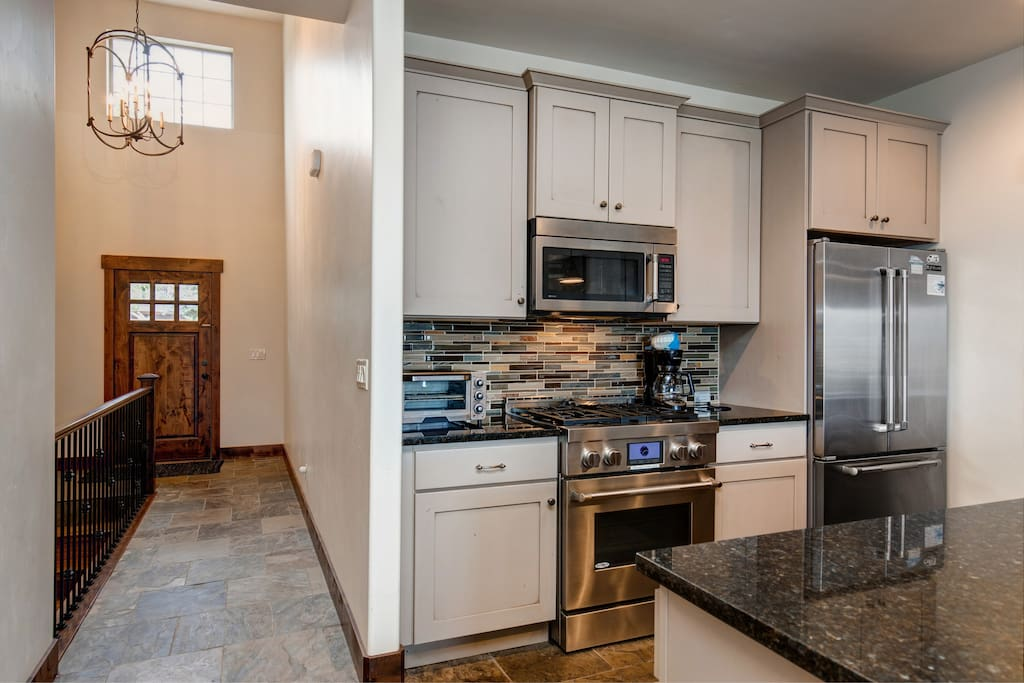 Main entry way straight ahead and fully equipped kitchen to the left