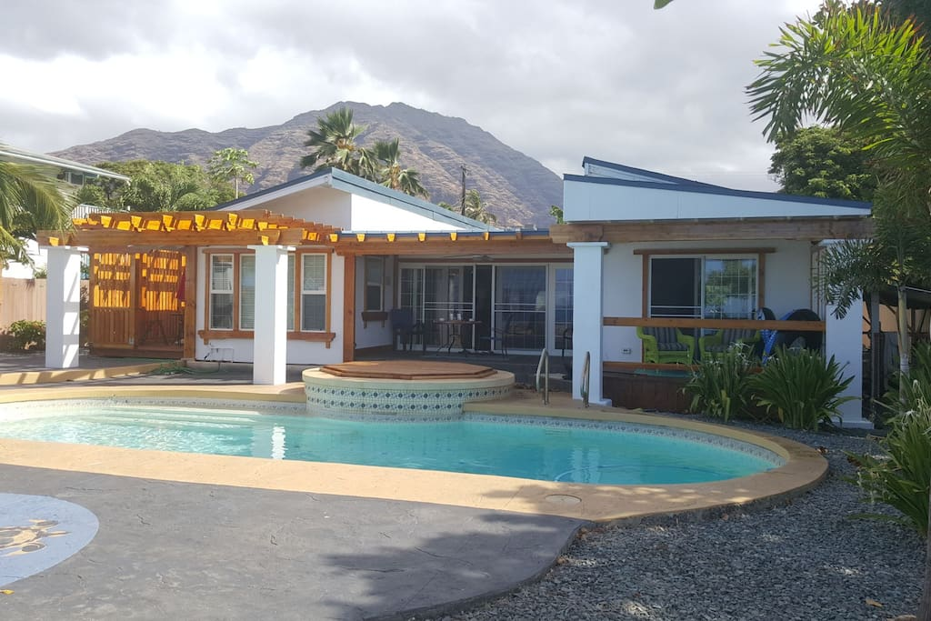 View from across the pool showing the outdoor seating areas and Makaha  mountains in the backround