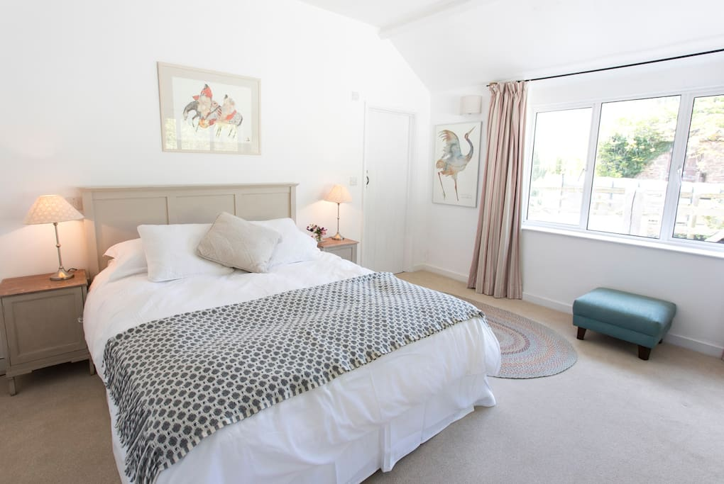 This downstairs super-kingsize bed can be split into two singles. the room has two large windows and an en-suite bathroom.