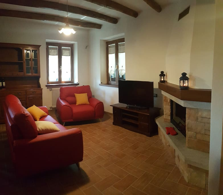 Salotto con divano, poltrona, tv hd e camino a legna con vetro - Living room with sofa, armchair, hd television and wood-burning fireplace with glass