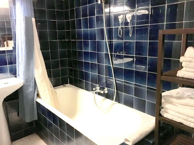 Salle de bain avec serviettes et tapis de bain