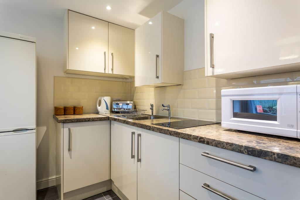 Recently installed kitchen with full size fridge/freezer, kettle, toaster, microwave and 2 ring halogen hob.