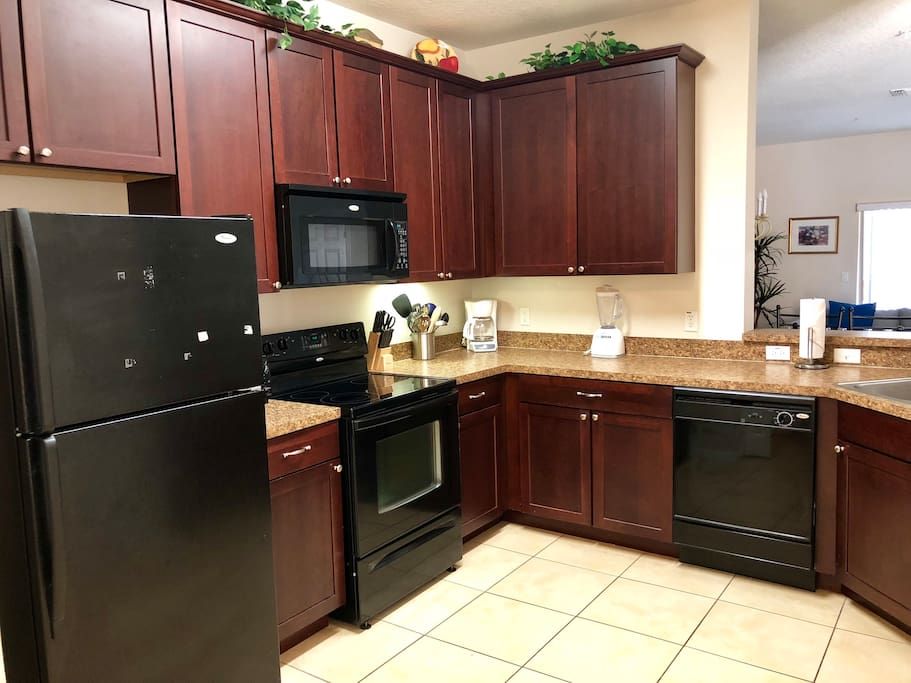 Fully furnished kitchen with microwave, stove, refrigerator, and supplies!