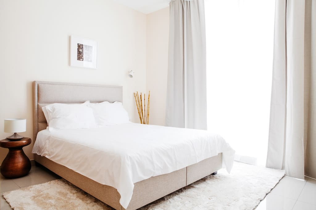 Natural light and beige tones dress the bedroom