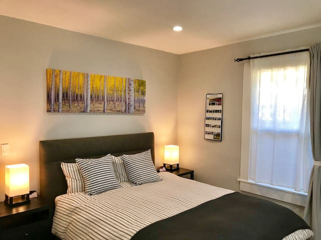 Bedroom with a queen size bed, facing east, on main floor, two night lamps with USB
