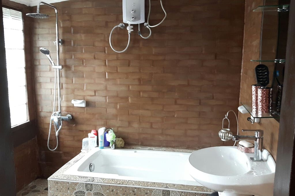 Master bedroom CR with bathtub /brick design and includes 8 towels for guest use.