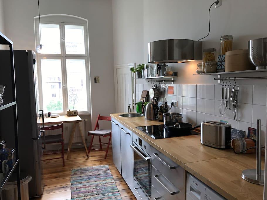 voll ausgestattete Küche mit Herd, Ofen, Geschirrspüler, Kühlschrank, Waschmaschine und Geschirr zum kochen