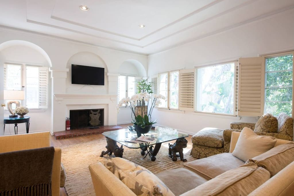 Living Room soaring 11 ft ceilings , grand wood burning fire place , authentic crown moldings & solid walnut wood floors . Custom made furniture by one of L.A's top design firms. Open a bottle of wine , relax to the Ipod music station or enjoy a nice movie