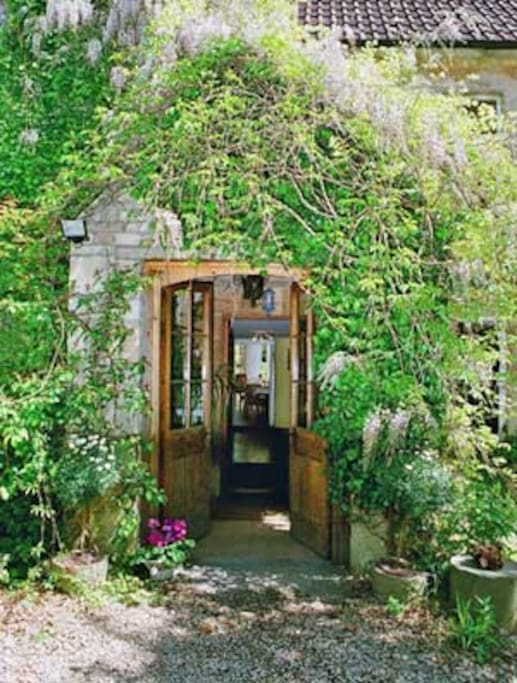 Welcome to Wisteria and red Virginia Creeper tumbling three floors from the chimneys to the porch at The Manor House in summer. Come in...