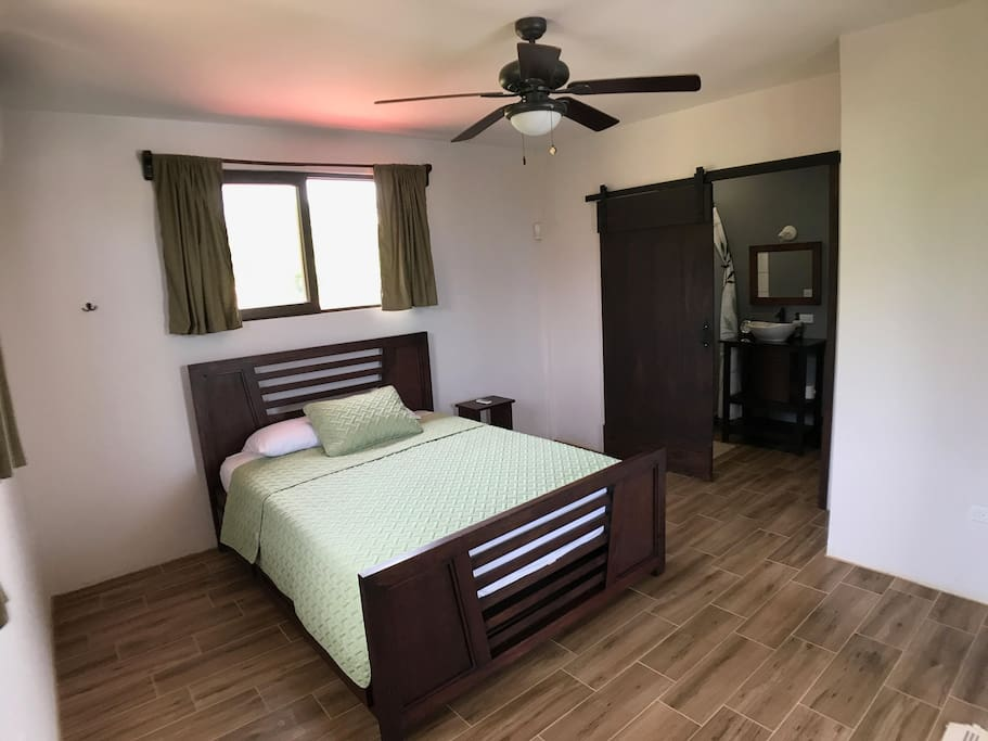 Master bedroom with queen bed and bathroom