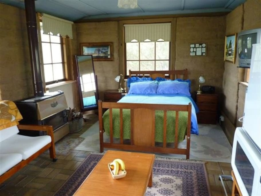 Cottage interior with bed and pot-belly stove