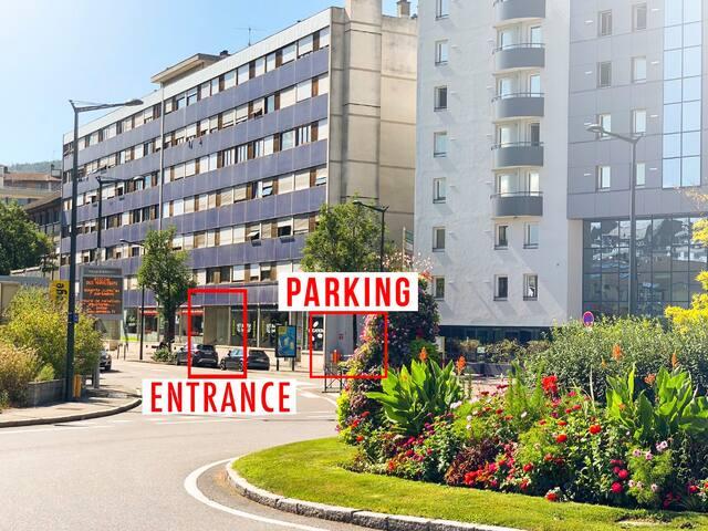 L'entrée de l'immeuble et l'entrée du parking aérien sécurisé avec barrière.