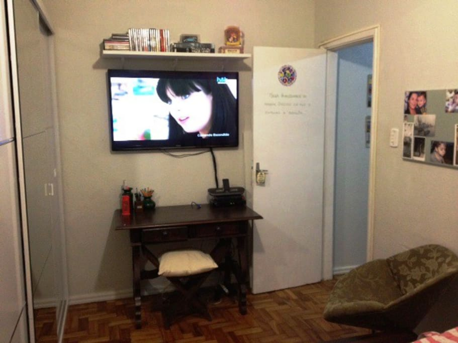 Another photo of the same room. Showing television, desk, chair and closet