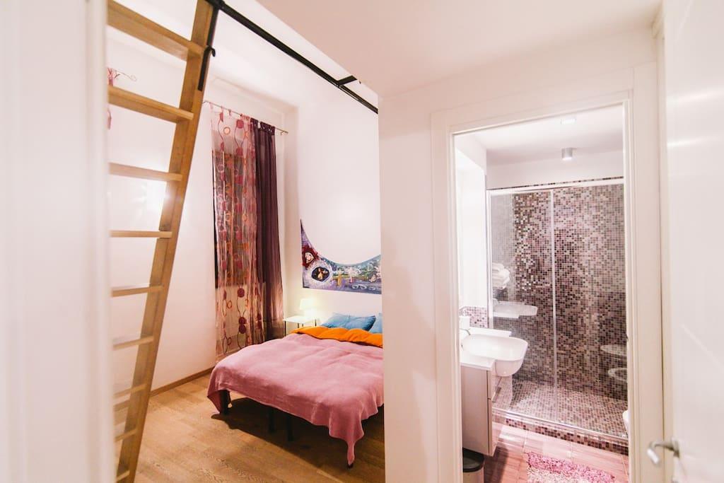 Uno scorcio sulla prima camera da letto e  il bagno in mosaico viola.  La scala porta al piccolo soppalco con un letto.