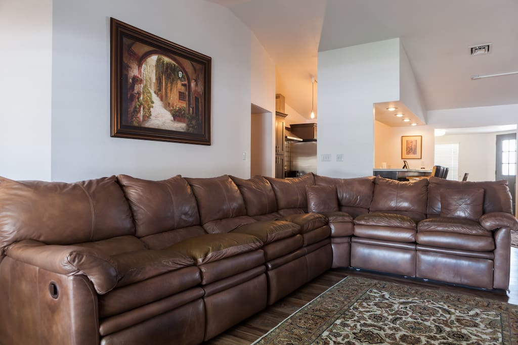 Formal living room w/ large sectional sofa and fireplace