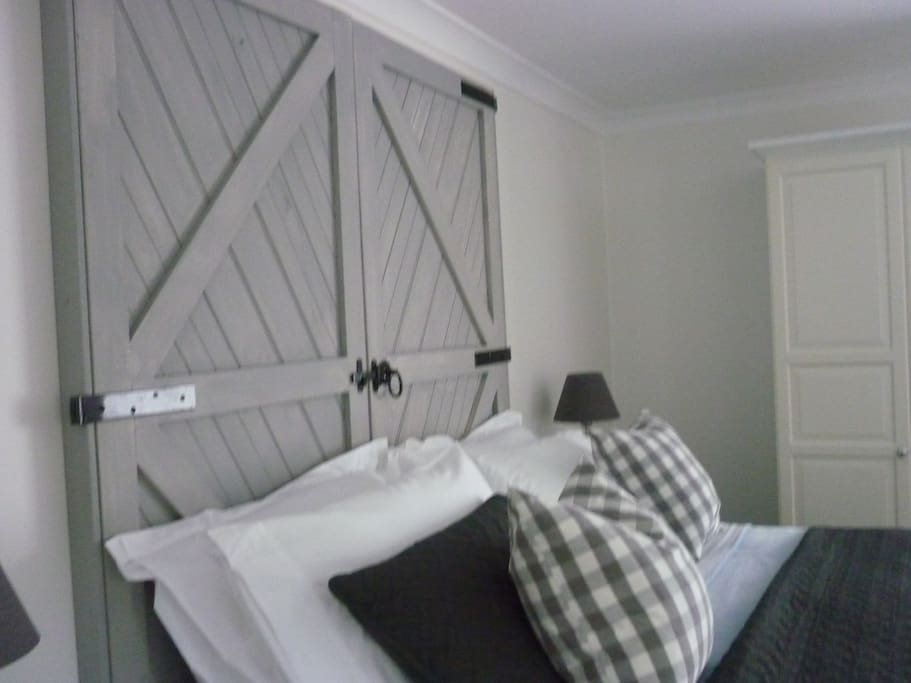 King bed with Barn door headboard. Has cosy vellux blanket for summer or super king size quilt in winter with electric blanket