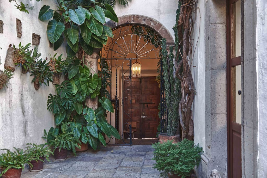 Front door, arched foyer entrance, wrought-iron gate, orchid- and fern-lined, stone-paved walkway to central patio