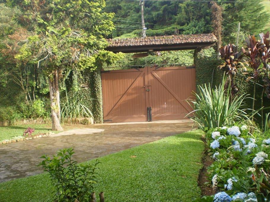 Vista de dentro do portão de entrada com jardim.