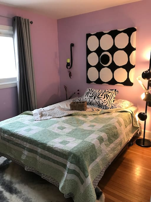 Master bedroom with queen size bed and memory foam topper. Alice in Wonderland hand- made quilt, Eq3 lamp and Marimekko wall art. You'll feel calm surrounded by these vintage lace lavender walls. And cushioned by all the pillows you could want.