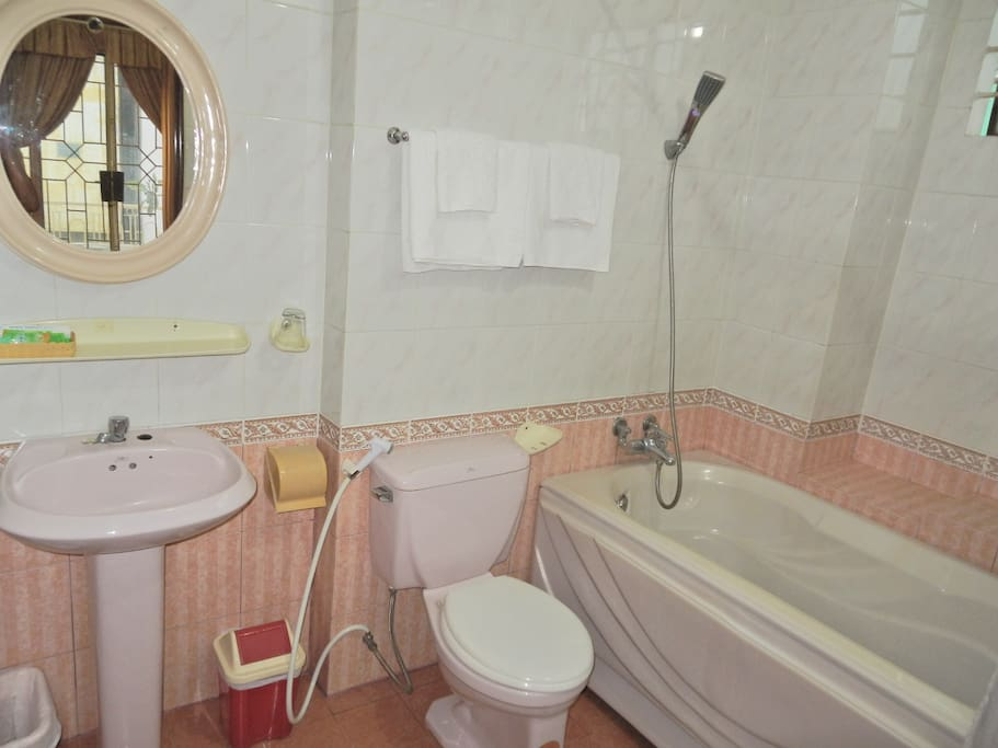 Private full bath with tub, fresh towels, and toiletries.