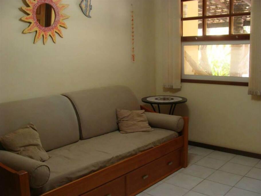 Sala com bicama, ventilador de teto e tela mosquiteira na janela e porta