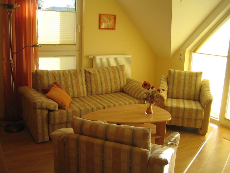 Die gemütliche Polsterecke im Wohnzimmer bietet eine weitere Schlafmöglichkeit.