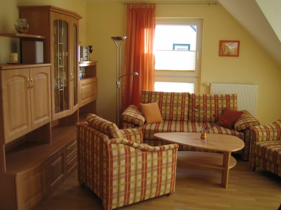 Im Wohnzimmer gibt es auch eine Wohnwand mit Glasvitrine und der Musikanlage.