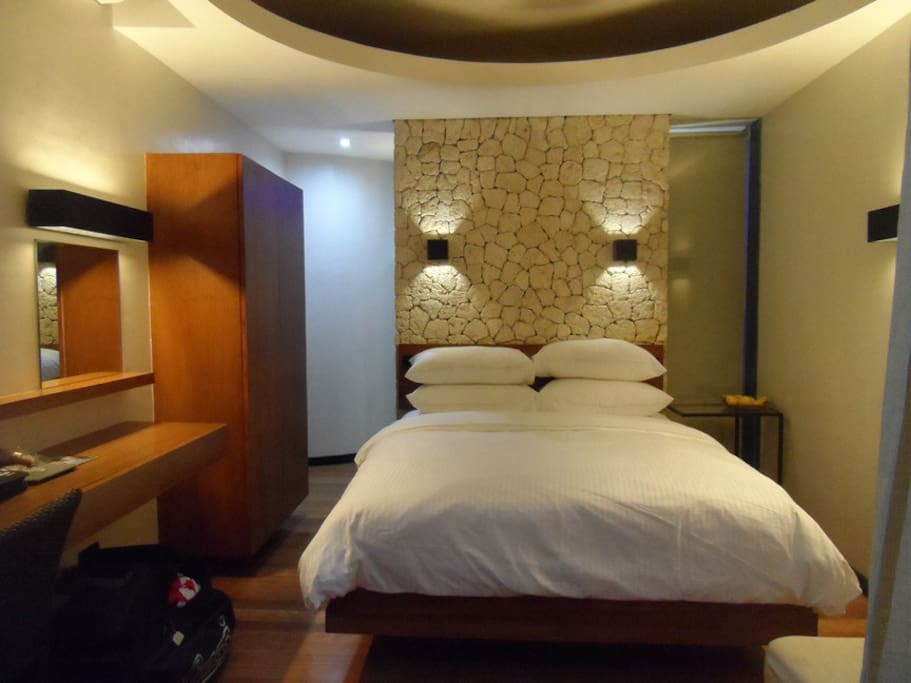 Bedroom featuring Boracay limestone (the source of Boracay famous fine white sand) wall in the centre of the room.  Wooden floors all the way to the bathroom.