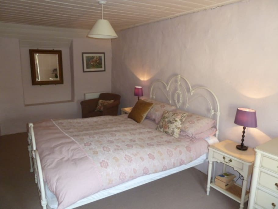 Main double bedroom with traditional iron bedstead and view to the garden