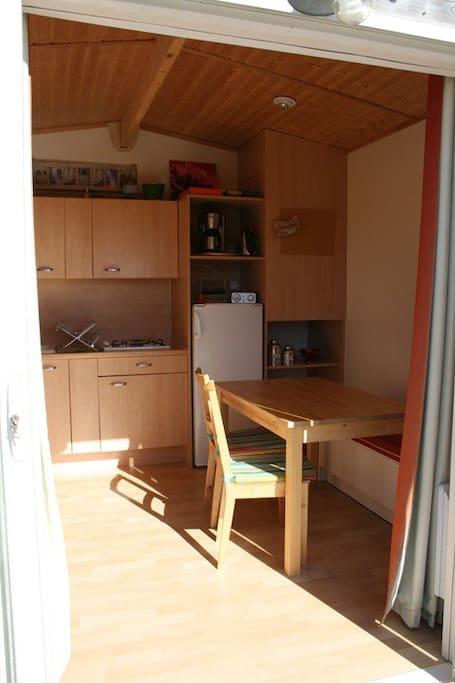 Petite cuisine équipée - salon avec accès direct baie vitrée sur la terrasse