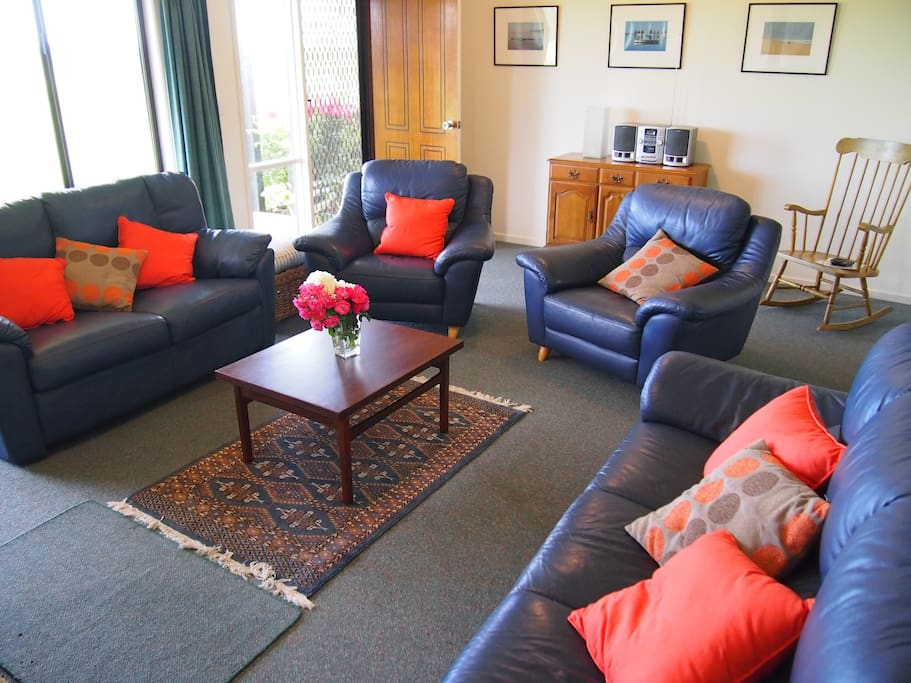 Comfortable leather lounge suite in the lounge room with water views