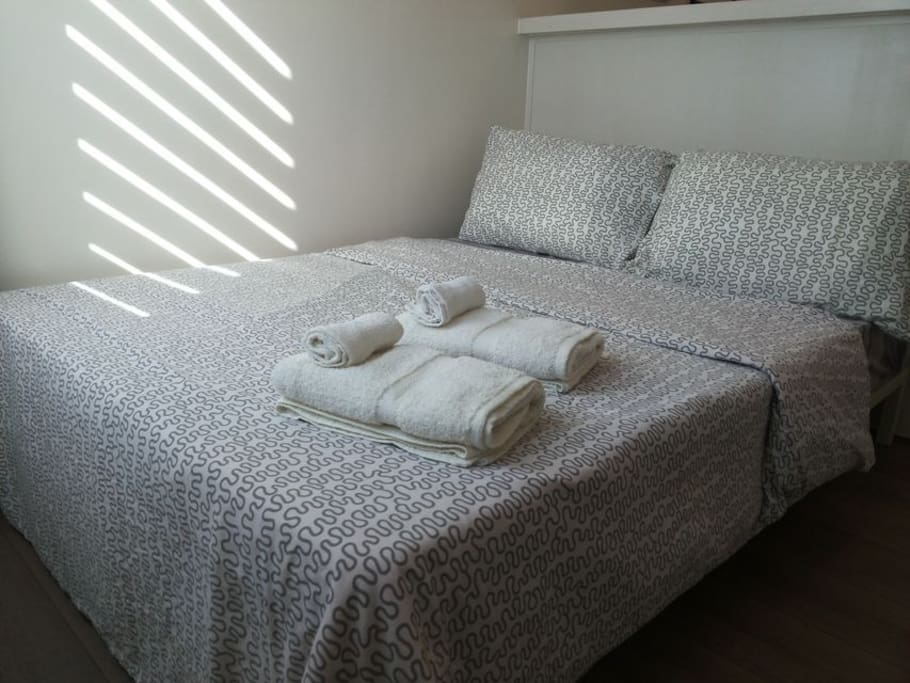 Queen size bed with newly washed towels