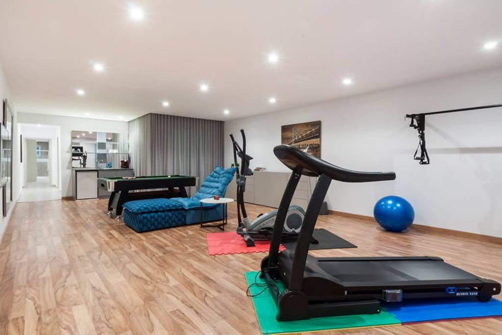 Gym and fitness area with bar and billiard table